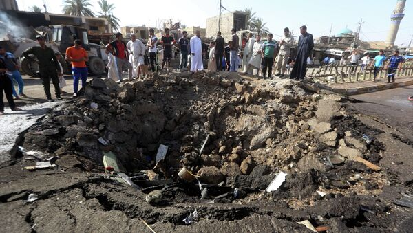 Iraqi men look at a crater left by a massive suicide car bomb attack carried out the previous day by the Islamic State group in the predominantly Shiite town of Khan Bani Saad, 20 km north of Baghdad, on July 18, 2015 - Sputnik International