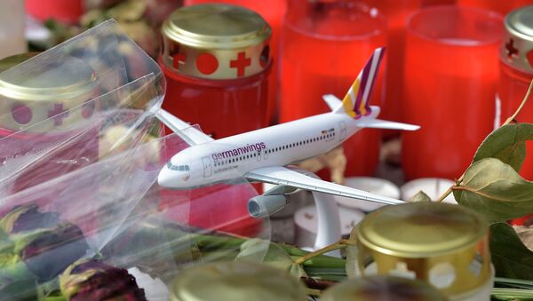 A model of a plane is placed between candles and flowers in front of the Germanwings headquarters in Cologne, western Germany for the victims of the plane crash two weeks ago in the French Alps, Tuesday, April 7, 2015 - Sputnik International