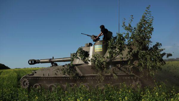 A Ukrainian serviceman rides atop an armored military vehicle to take their positions near Donetsk, eastern Ukraine, Sunday, June 7, 2015 - Sputnik International