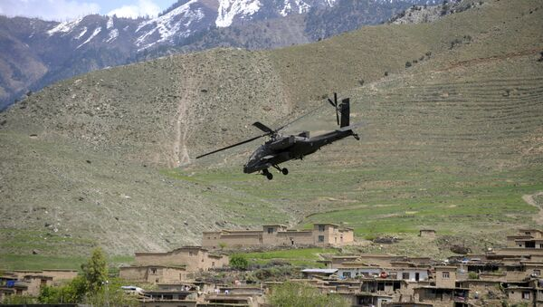 A US Army AH-64 Apache helicopter flies over a village in Naray, in Afghanistan's eastern Kunar province on April 16, 2009 - Sputnik International