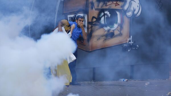 A couple runs away from tear gas used by riot police to disperse demonstrators during a protest in central Istanbul, Turkey, July 20, 2015. - Sputnik International