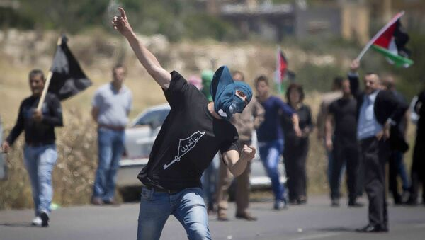 A Palestinian throws a stone at Israeli troops during clashes after a rally marking Nakba Day at Hawara checkpoint near the West Bank city of Nablus. - Sputnik International