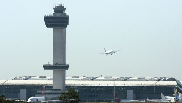 An aircraft flies past the control tower as it prepares to land at New York's John F Kennedy Airport, May 25, 2015 - Sputnik International