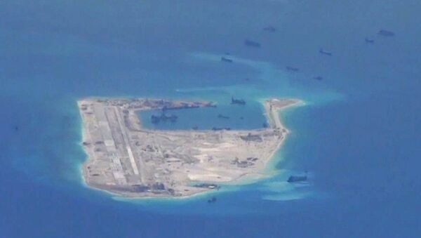 Chinese dredging vessels are purportedly seen in the waters around Fiery Cross Reef in the disputed Spratly Islands in the South China Sea in this still file image from video taken by a P-8A Poseidon surveillance aircraft provided by the United States Navy - Sputnik International
