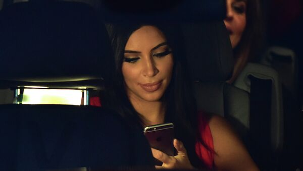 US reality TV star Kim Kardashian looks at her iPhone as she sits in a car after visiting the genocide memorial, which commemorates the 1915 mass killing of Armenians in the Ottoman Empire, in Yerevan on April 10, 2015 - Sputnik International