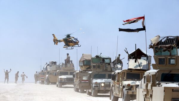 An Iraqi helicopter flies over military vehicles in Husaybah, in Anbar province July 22, 2015 - Sputnik International