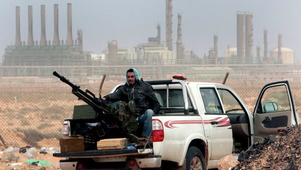 In this March 5, 2011 file photo, an anti-government rebel sits with an anti-aircraft weapon in front an oil refinery, after the capture of the oil town of Ras Lanouf, eastern Libya. - Sputnik International