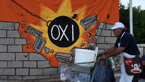 A street vendor pushes his trolley as he passes a banner, depicting a wrecking ball that reads: NO and destroying a wall with anti-austerity measures, in Athens, Wednesday, July 22, 2015. - Sputnik International