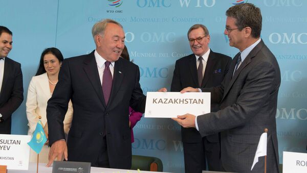 WTO Director general Roberto Azevedo (R) offers Kazakhstan's country sign to President Nursultan Nazarbayev after the accession ceremony at the World Trade Organization (WTO) headquarters in Geneva, Switzerland July 27, 2015 - Sputnik International
