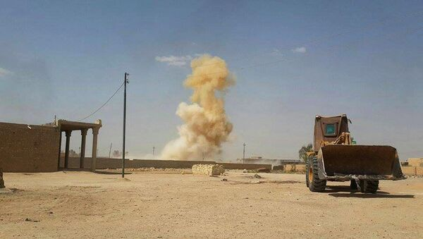 In this Sunday, July 19, 2015 photo, smoke rises following a U.S.-led coalition airstrike against Islamic State group positions as a bulldozer belonging to the Iraqi security forces backed by Shiite and pro-government Sunni fighters is deployed for fighting against Islamic State group militants in Tash district in southern Ramadi, Anbar province, Iraq - Sputnik International