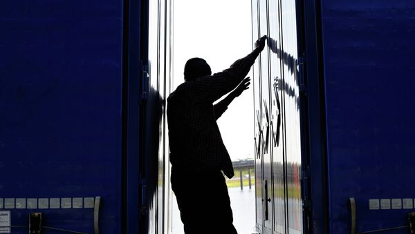 A migrant stands between two trailers of a lorry as he attempts to cross the English Channel, - Sputnik International