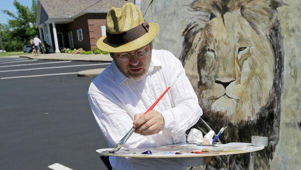 Mark Balma works on a mural of Cecil the lion outside Dr. Walter James Palmer's dental office in Bloomington, Minnesota. - Sputnik International