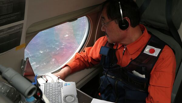Communications specialist Hidetaka Sato on a Japan Coast Guard Gulfstream aircraft, looks out of a window searching for the missing Malaysia Airlines Flight MH370 in Southern Indian Ocean, near Australia, Tuesday, April 1, 2014. - Sputnik International
