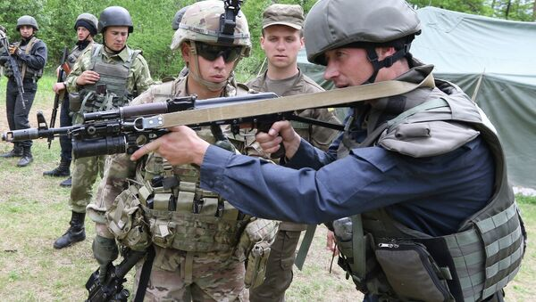 US soldier, left, instructs a Ukrainian soldier during joint training exercises on the military base in the Lviv region. - Sputnik International
