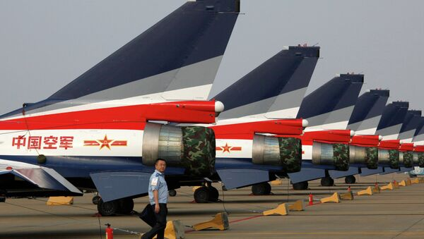 A man walks pasT the Chinese-made J-10 jet fighters on display at the 8th China International Aviation and Aerospace Exhibition (Zhuhai Airshow) in Zhuhai. - Sputnik International