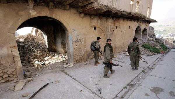 In this Thursday Jan. 29, 2015 photo, fighters of the Turkey-based Kurdish Workers' Party (PKK) walk in the damaged streets of Sinjar, Iraq - Sputnik International