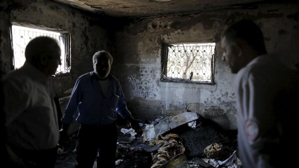 Palestinians inspect a house which was set on fire in a suspected attack by Jewish extremists in Duma village near the West Bank city of Nablus - Sputnik International