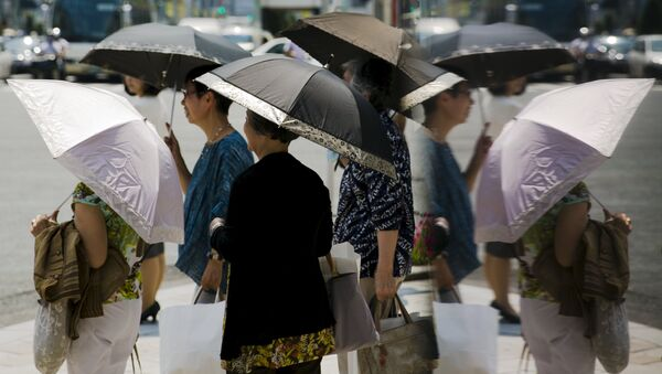 Women hold parasols as they wait at a pedestrian crossing on a hot day in Tokyo - Sputnik International