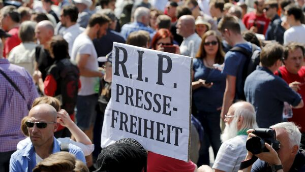 A demonstrator holds up a placard which reads Rest in Peace freedom of press! during a rally to protest against a criminal complaint by the domestic intelligence agency, the Office for the Protection of the Constitution (BfV), over articles about it that appeared on the Netzpolitik.org blog, in Berlin, Germany, August 1, 2015 - Sputnik International