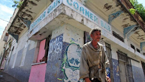 A homeless man stands in front of a closed down business in Puerta de Tierra in the outskirts of Old San Juan, Puerto Rico, Sunday, Aug. 2, 2015. Mired in a 10 year old economic crisis, Puerto Rico failed to pay a $58 million bond payment due Saturday. If defaults continue, analysts say Puerto Rico will face numerous lawsuits and increasingly limited access to markets, putting a recovery even more out of reach. - Sputnik International