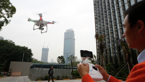 An employee from DJI Technology Co. demonstrates the remote flying with his Phantom 2 Vision+ drone in Shenzhen, south China's Guangdong province. - Sputnik International