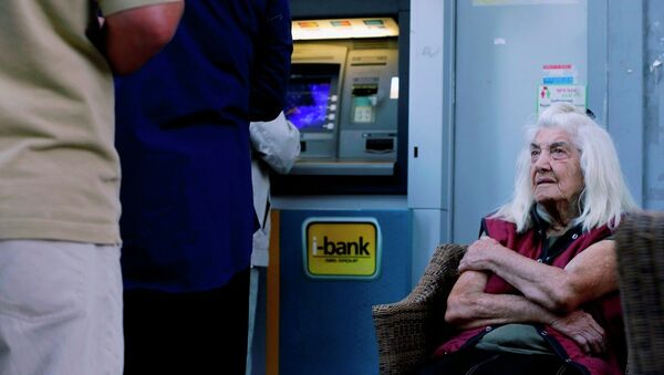 A pensioner looks at customers who use an ATM as she sits outside a bank in Athens, Wednesday, July 1, 2015. - Sputnik International