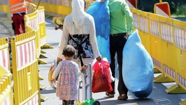 Asylum seekers walk outside the central refugee camp in Giessen, Germany, Monday, Aug. 3, 2015. - Sputnik International