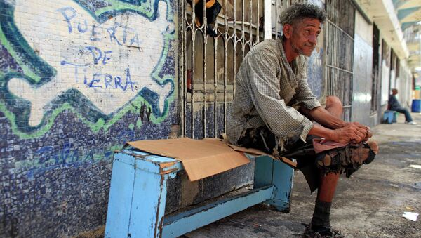 A homeless man improvises his shoes with pieces of cloth in front of a closed down business in Puerta de Tierra in the outskirts of Old San Juan, Puerto Rico, Sunday, Aug. 2, 2015 - Sputnik International