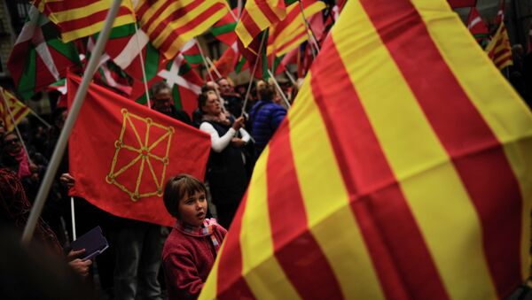 Pro-independence demonstrators of Catalonia and Basque Country raise their regional flags. File photo - Sputnik International