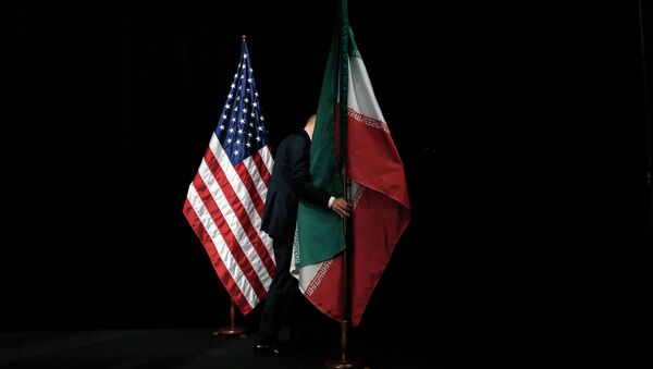 A staff member removes the Iranian flag from the stage after a group picture with foreign ministers and representatives of Unites States, Iran etc. - Sputnik International