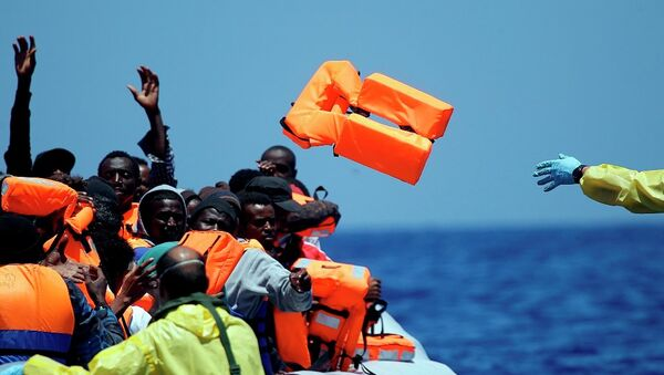 A Belgian nav.y sailor passes life vests to migrants sitting in a rubber boat as they approach the Belgian Navy Vessel Godetia during a search and rescue mission in the Mediterranean Eea off the Libyan coasts, Tuesday, June 23, 2015 - Sputnik International