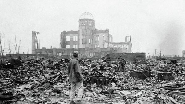 This Sept. 8, 1945 picture shows an allied correspondent standing in the rubble in front of the shell of a building - Sputnik International