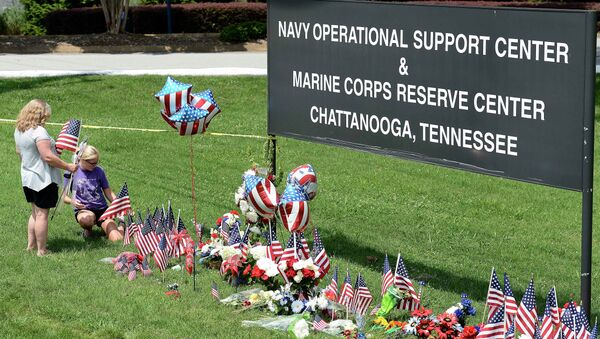 Two women place American flags by a makeshift memorial at the entrance to the Naval Operational Support Center and Marine Reserve Center in Chattanooga, Tennessee. - Sputnik International
