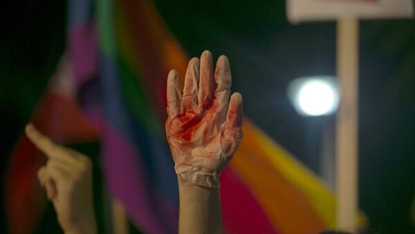 A protester holds up a glove covered in red during a protest against the violence towards the gay community in Tel Avi - Sputnik International
