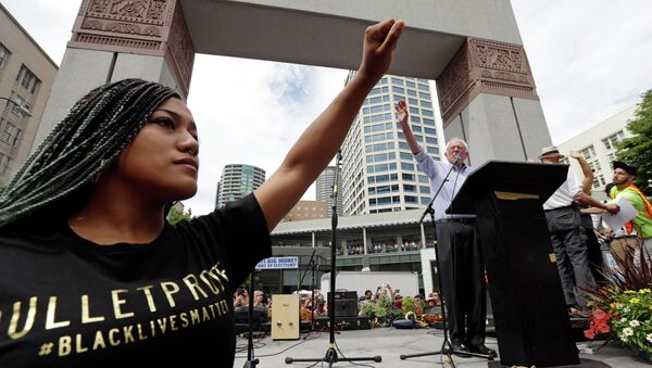 Mara Jacqueline Willaford, left, holds her fist overhead as Democratic presidential candidate Sen. Bernie Sanders, I-Vt., waves to greet the crowd before speaking at a rally Saturday, Aug. 8, 2015, in downtown Seattle. - Sputnik International
