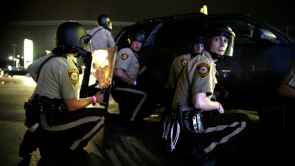 Police take cover behind a vehicle during a protest in Ferguson, Mo., Sunday, Aug. 9, 2015 - Sputnik International