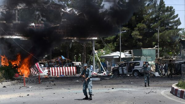 An Afghan policeman keeps watch at the site of a powerful truck bomb in Kabul on August 10, 2015 - Sputnik International
