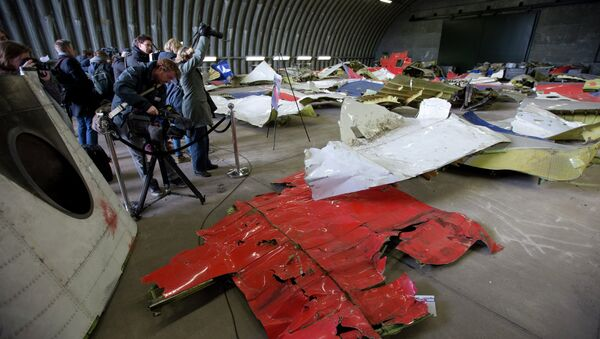 Journalists take images of parts of the wreckage of the Malaysia Airlines Flight 17 displayed in a hangar at Gilze Rijen airbase, Netherlands, Tuesday, March 3, 2015 - Sputnik International