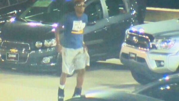 Surveillance video on the lot of a car dealership shows Christian Taylor, 19, of Arlington, Texas, jumping on vehicles August 7 before officers arrived. - Sputnik International