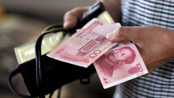 A customer holds a 100 Yuan note at a market in Beijing, August 12, 2015 - Sputnik International