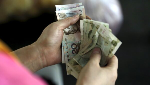 A customer counts Chinese Yuan notes at a market in Beijing, August 12, 2015 - Sputnik International