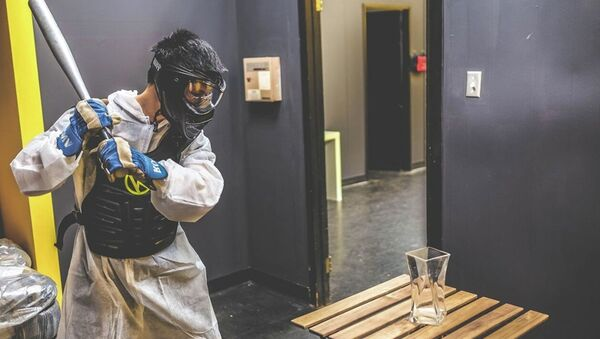 A customer prepares to swing a baseball bat at a vase in the Rage Room at Battle Sports in Toronto, Canada. - Sputnik International