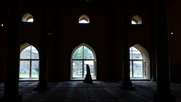 A Kashmiri Muslim woman walks after praying inside the grand mosque Jamia Masjid during Ramadan in downtown Srinagar on June 25, 2015. File photo - Sputnik International