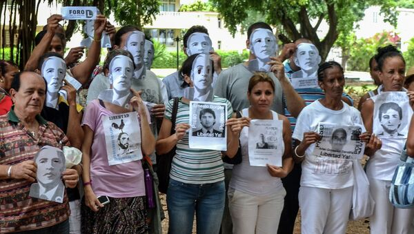 Cuban dissidents pose wearing masks depicting US President Barack Obama and holding pictures of imprisoned dissidents as they protest against the reopening of the US embassy in the island, during a meeting of the Ladies in White human rights group in a park of Havana, on August 9, 2015 - Sputnik International