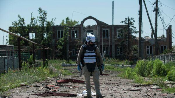 An OSCE monitor checks the territory for mines during a patrol in Shyrokyne, Donetsk region eastern Ukraine, Saturday, July 4, 2015 - Sputnik International