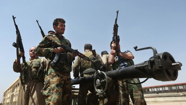 In this Wednesday, June 25, 2014 file photo, Kurdish peshmerga fighters take positions on the front line with militants from the al-Qaida-inspired Islamic State in Iraq and the Levant, in Tuz Khormato, 100 kilometers (62 miles) south of Kirkuk, northern Iraq - Sputnik International