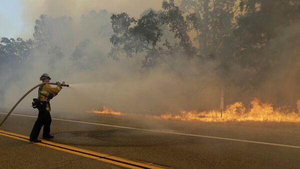 A firefighter sprays a hose at a fire burning along Morgan Valley Road near Lower Lake, Calif - Sputnik International
