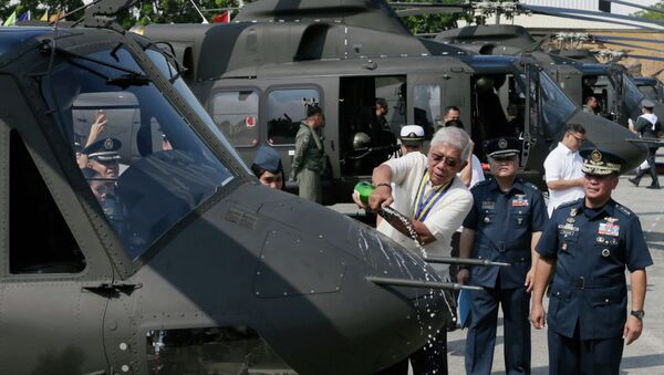 Philippine National Defense Chief Voltaire Gazmin pours champagne on a Bell-412EP helicopter. - Sputnik International