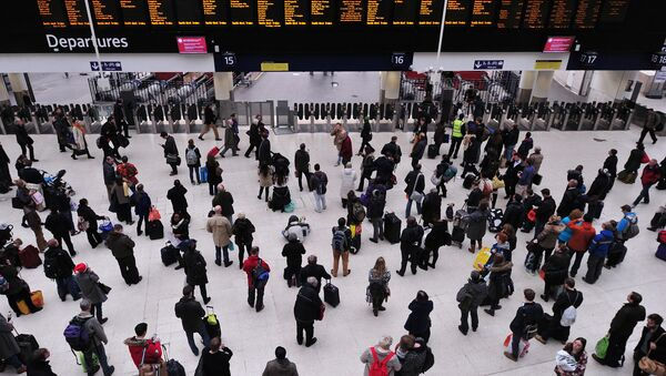 People wait with their luggage by the departure boards in Waterloo train station in central London - Sputnik International