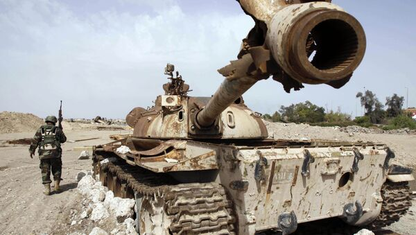 An Iraqi soldier is seen near an Iraqi Army tank, which was destroyed in the US-led invasion, in Basra, Iraq's second-largest city, 550 kilometers (340 miles) southeast of Baghdad, Iraq, Thursday, April 9, 2009 - Sputnik International